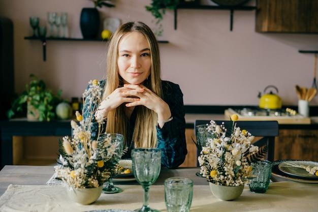 Linda garota caucasiana senta-se na mesa decorada