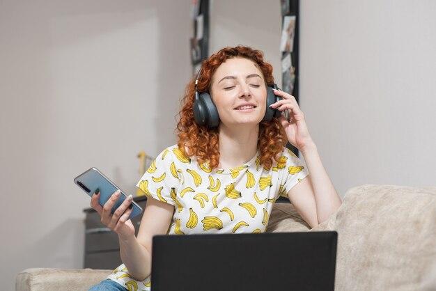 Linda garota caucasiana sentada no sofá em casa ouvindo música em fones de ouvido