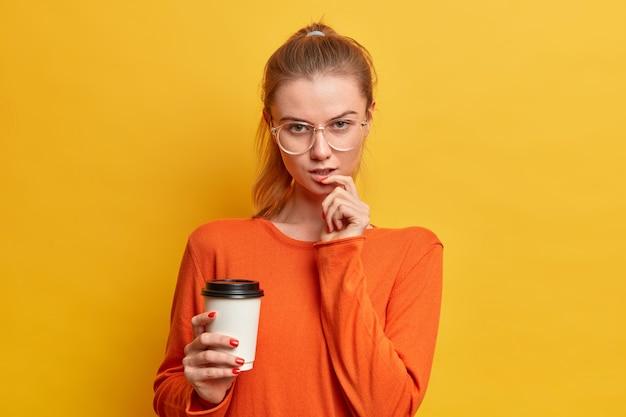 Linda garota caucasiana séria olhando seriamente para a câmera tomando café para viagem