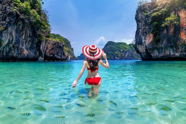 Linda garota cercada por peixes no mar de andaman, krabi, tailândia.