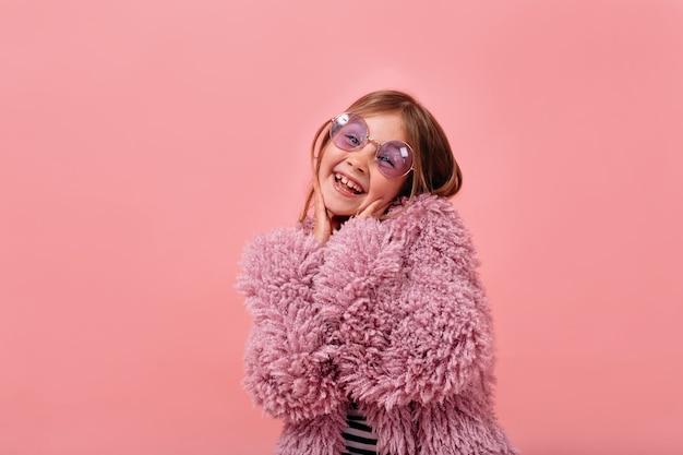 Linda garota charmosa de 6 anos usando pelo de pele violeta e óculos redondos, posando com emoções felizes