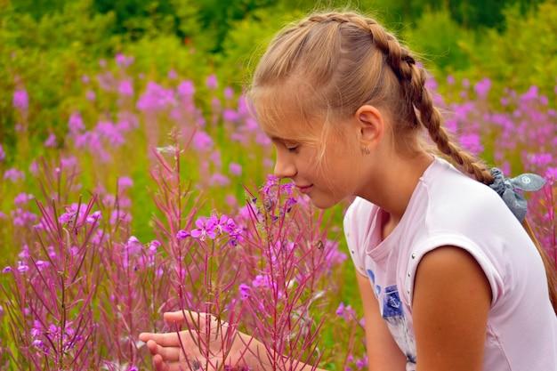 Linda garota cheira flores cor de rosa no jardim