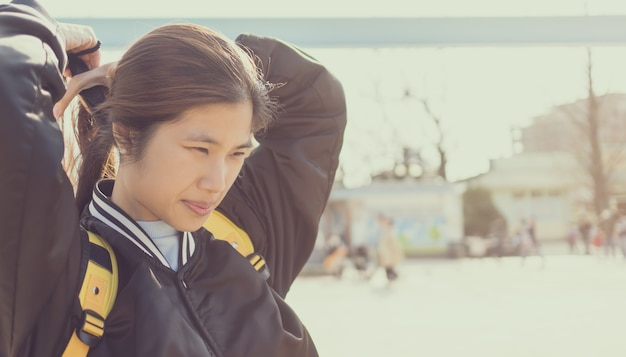 Linda garota chinesa longa em jaqueta de beisebol
