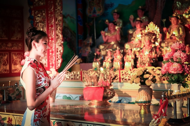 Linda garota chinesa vestindo um terno cheongsam tradicional, queimando incensos e prestando homenagem e orando ao deus chinês pela sorte