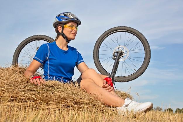 Linda garota ciclista sentada na grama seca na bicicleta =