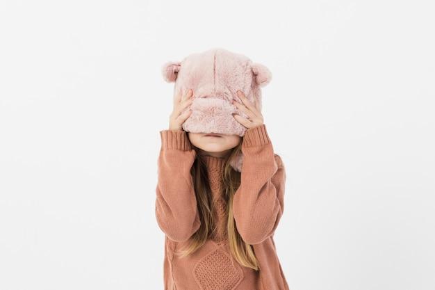 Linda garota, cobrindo o rosto com chapéu de inverno