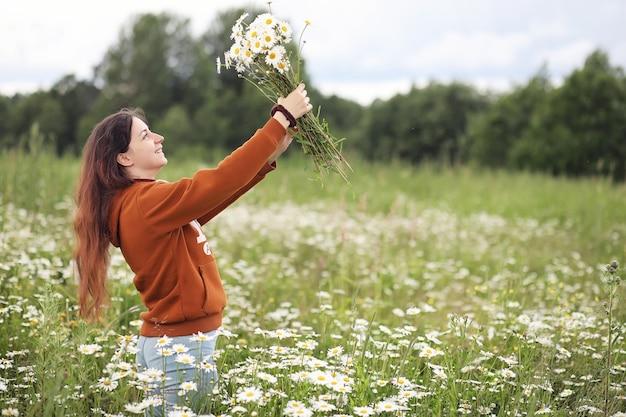 Linda garota coleta margaridas em um dia de verão em um campo