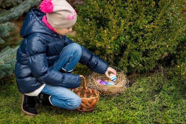 Linda garota coletando ovos de páscoa coloridos na cesta no quintal