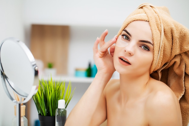 Linda garota coloca manchas sob os olhos no banheiro