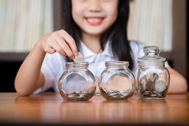 Linda garota colocando dinheiro moedas em vidro, salvando o conceito de dinheiro