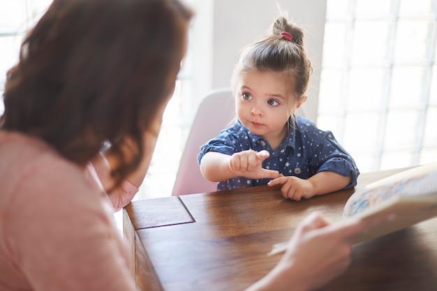 Linda garota com a mãe lendo um livro