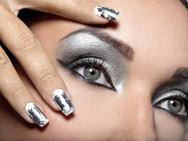 Linda garota com a maquiagem prateada de olhos e unhas de metal.
