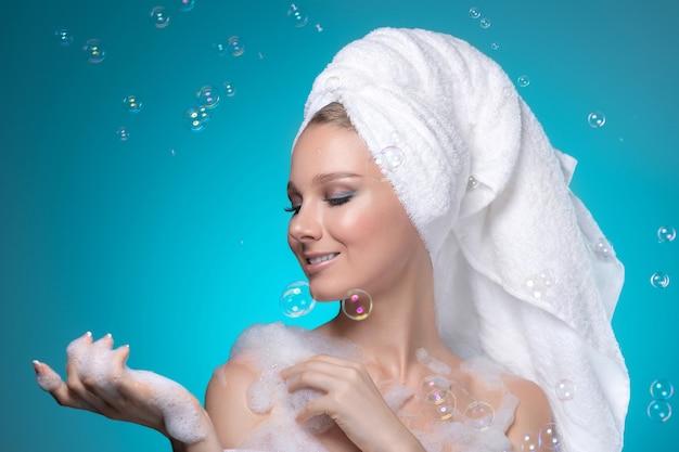 Linda garota com a toalha na cabeça e a espuma de banho nas mãos sonhando.