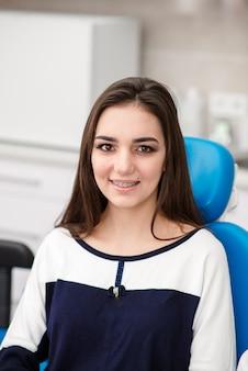 Linda garota com aparelho sorri na odontologia.