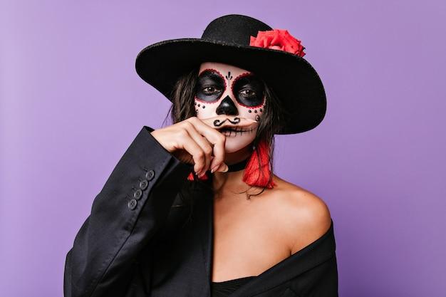 Linda garota com arte incomum no rosto em estilo mexicano, segurando o dedo com bigode pintado na frente dos lábios.