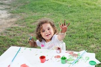 Linda garota com as mãos pintadas em tintas coloridas