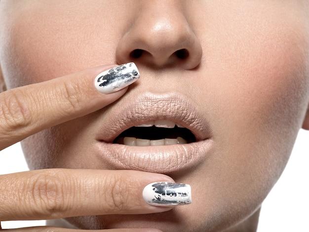 Linda garota com as unhas de metal prateadas.