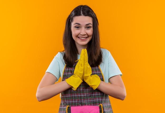 Linda garota com avental e luvas de borracha segurando as palmas das mãos juntas como um gesto de namaste, sentindo-se grata e feliz
