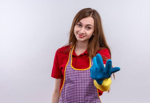 Linda garota com avental e luvas de borracha sorrindo fazendo um gesto com a mão