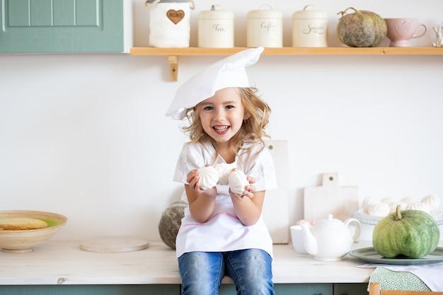 Linda garota com bolos na cozinha em casa