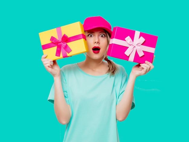 Linda garota com boné rosa e camiseta azul com caixas de presentes de férias sobre fundo verde.
