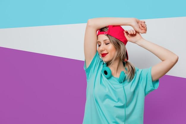 Linda garota com boné rosa e camiseta azul com fones de ouvido em fundo roxo e azul.