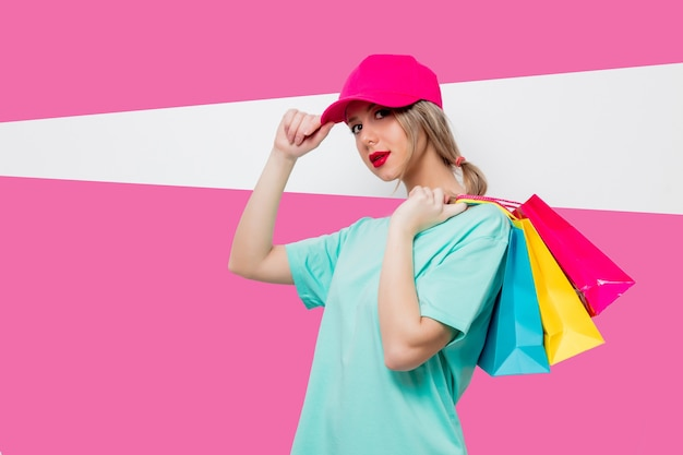 Linda garota com boné rosa e camiseta azul com sacolas de compras no fundo rosa.