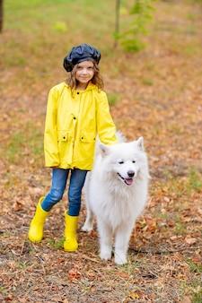 Linda garota com botas de borracha amarelas e capa de chuva em uma caminhada, brinca com um lindo cachorro samoiedo branco no parque outono.