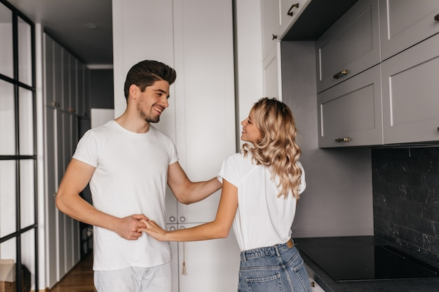 Linda garota com cabelo brilhante dançando com o namorado. cara bonito de cabelos escuros de mãos dadas com a esposa.