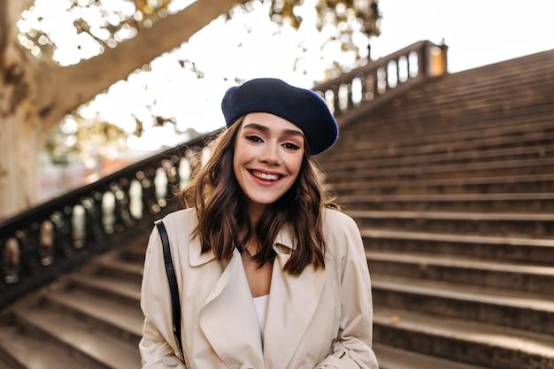 Linda garota com cabelo castanho, boina e sobretudo bege, sorrindo e posando ao ar livre, encostada em escadas velhas durante o dia