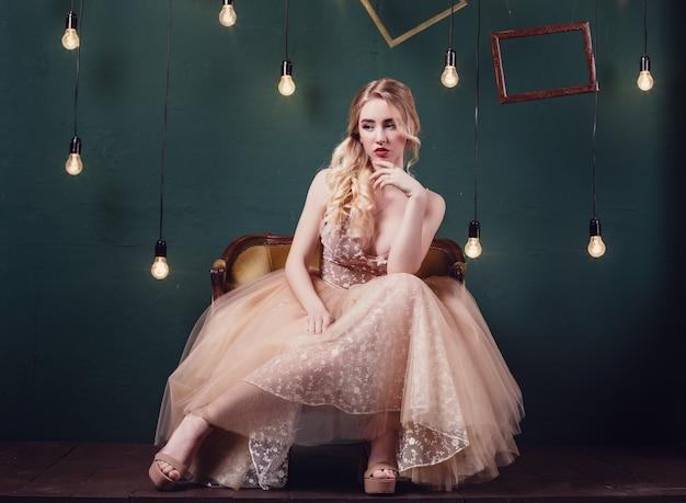 Linda garota com cabelo castanho usando um luxuoso vestido bege,