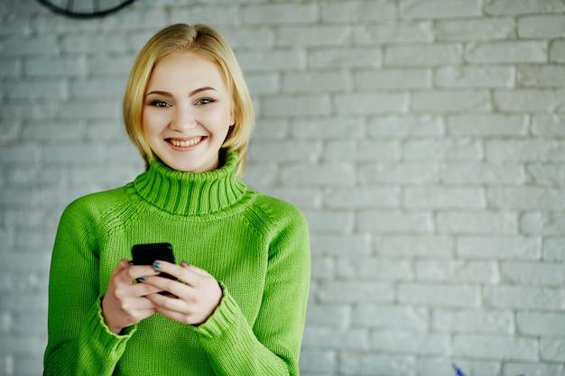 Linda garota com cabelo claro, suéter verde, sentado no café com o telefone móvel, conceito freelance, compras online, retrato.