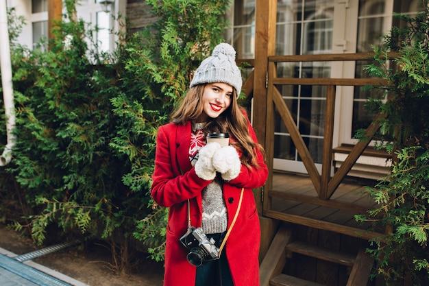 Linda garota com cabelo comprido, com casaco vermelho e chapéu de malha na casa de madeira. ela segura o café para viagem com luvas brancas, sorrindo amigavelmente.