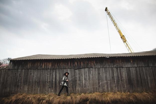 Linda garota com cabelo comprido e chapéu preto, fica no fundo da casa de madeira antiga vintage