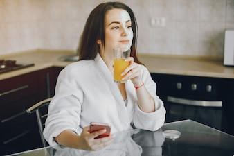 Linda garota com cabelo comprido e roupão branco, sentado em casa na cozinha à mesa