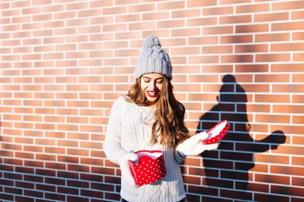 Linda garota com cabelo comprido em chapéu de malha, suéter branco quente, luvas na parede do lado de fora. ela está surpresa com o presente de natal em suas mãos.