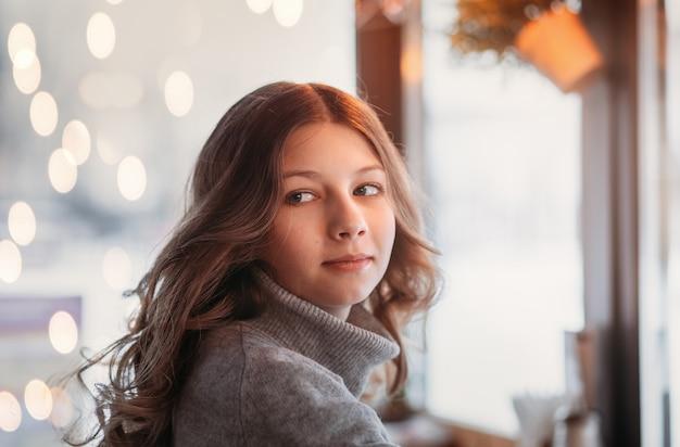 Linda garota com cabelo comprido em um café à noite, close-up