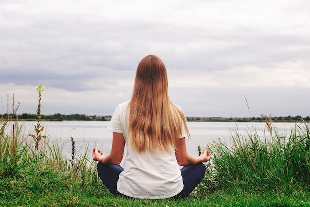 Linda garota com cabelo comprido está sentado na beira da praia. a vista de trás. pôr do sol. paz e tranquilidade. yoga à beira do lago