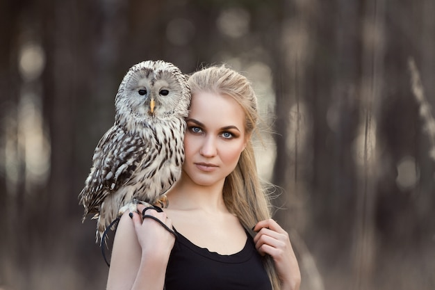 Linda garota com cabelo comprido natureza, segurando a coruja