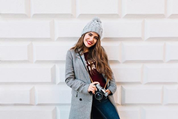 Linda garota com cabelo comprido no casaco cinza e chapéu de malha na parede cinza. ela segura a câmera nas mãos e parece ter gostado.