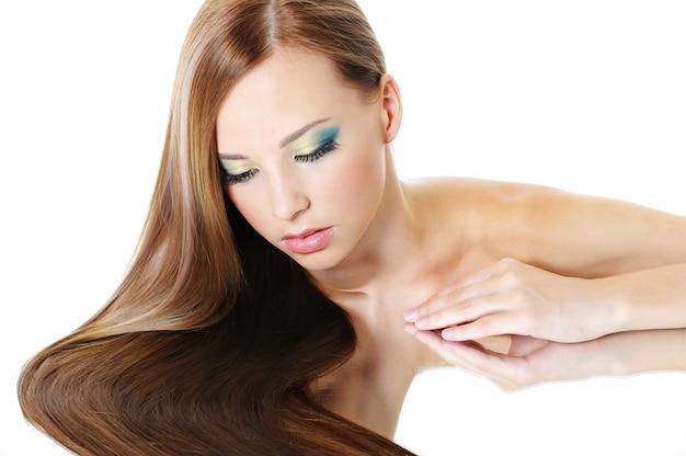 Linda garota com cabelo comprido saudável olhando para baixo no espelho