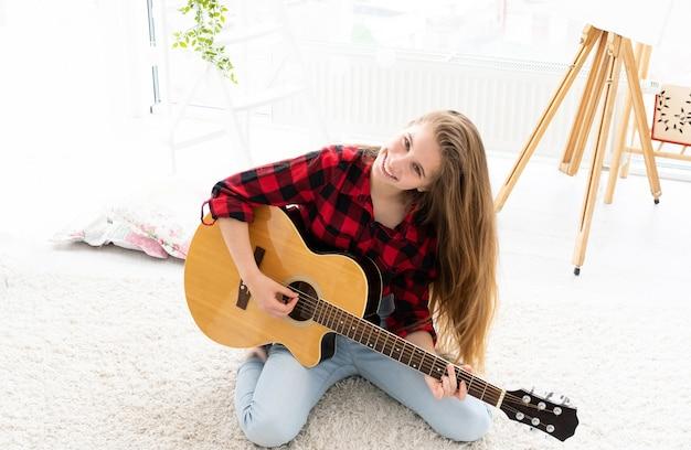 Linda garota com cabelo comprido solto tocando guitarra em uma sala iluminada