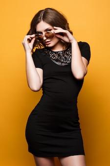 Linda garota com cabelo curto, sorrindo e segurando os óculos de sol. maquiagem de noite, batom nude, sorriso branco