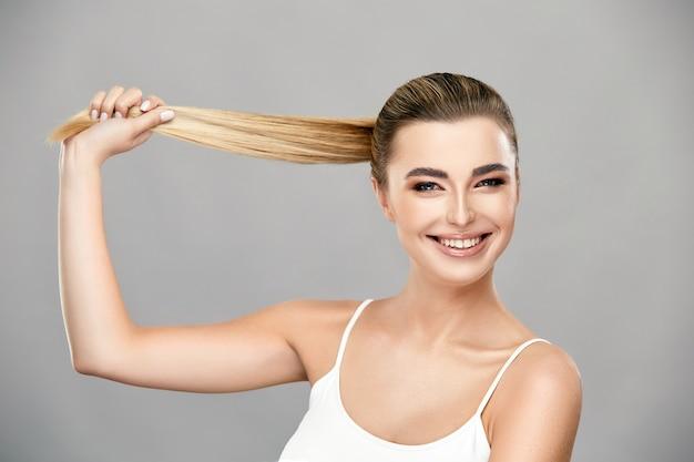 Linda garota com cabelo de cor clara natural sorrindo, vestindo camisa branca, linda garota saudável com cabelo loiro bem preso