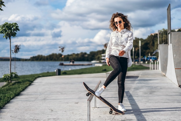 Linda garota com cabelo encaracolado com skate no parque