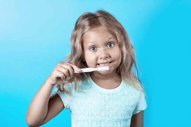 Linda garota com cabelo encaracolado escovar os dentes com escova de dentes branca em um azul.