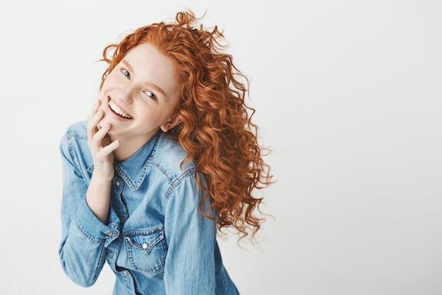 Linda garota com cabelo encaracolado vermelho rindo sorrindo.