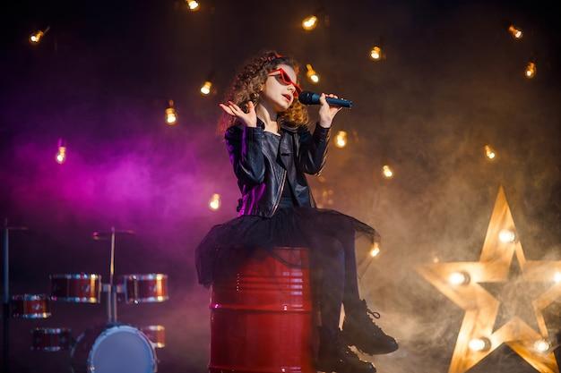 Linda garota com cabelo encaracolado, vestindo jaqueta de couro e óculos de sol vermelhos canta em um microfone sem fio para karaokê no estúdio de gravação