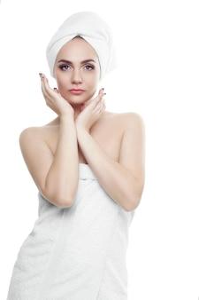Linda garota com cabelo escuro e sobrancelhas escuras, usando uma toalha branca na cabeça, segurando as mãos perto do rosto. maquiagem leve. retrato de uma linda mulher de 20-25 anos com uma toalha na cabeça