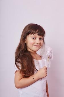 Linda garota com cabelo loiro come um pirulito, caramelo redondo na vara nas mãos de uma garota sorridente e alegre. menina com cabelo comprido lambe o pirulito.